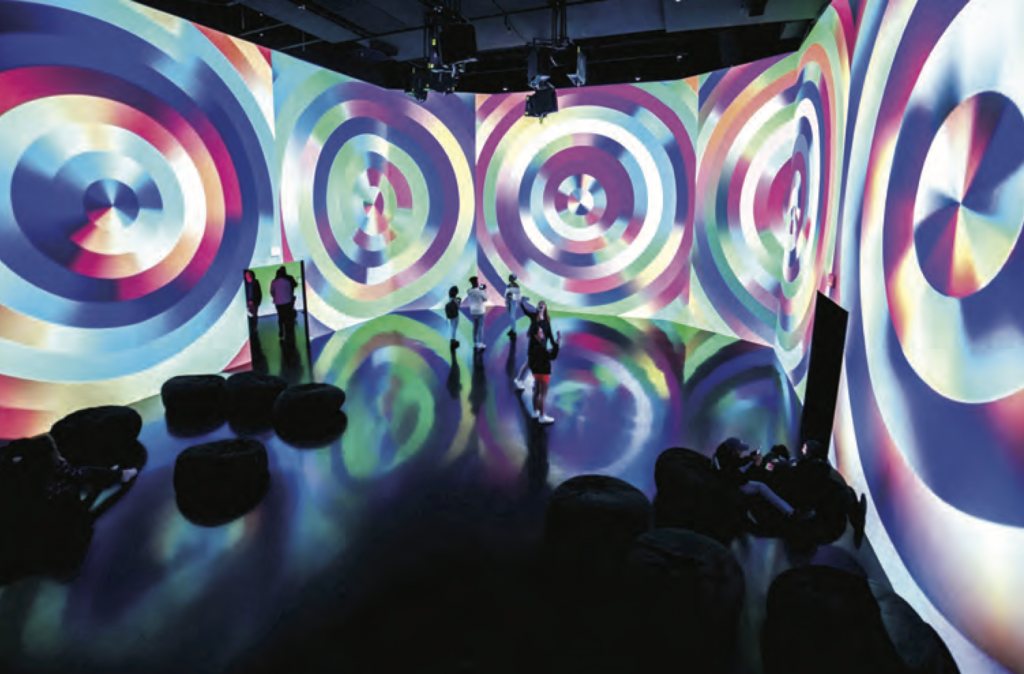 Birds-eye view of large gallery room with large bean bag cushions scattered on the floor and 5 people in the center of the room taking photos of and with the space. Projections on each wall of colorful circular psychedelic-like pattern.