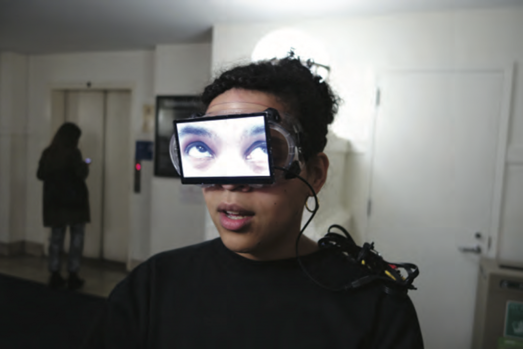 Background in gallery setting with white walls, white door on right side and elevator on left side and a figure standing infront of the elevator. In the foreground a closeup of a woman with curly hair in bun, wearing a black long sleeve shirt, and mouth open wearing goggles with a screen attached over her eyes. On the screen it shows a close up of a person's eyes looking up and to the right.